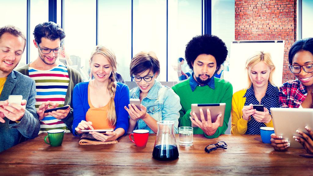 Persone al tavolo con smartphone e tablet