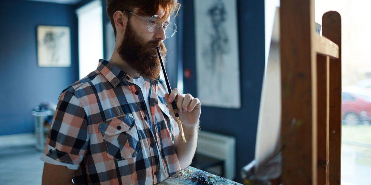 artista che dipinge nella sua galleria d'arte