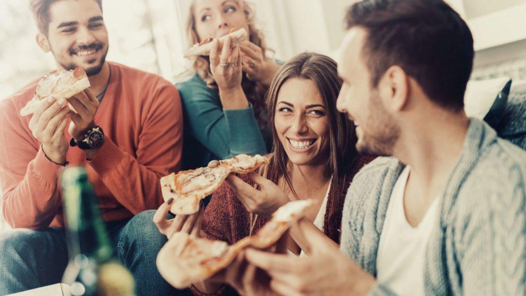 amici che mangiano una pizza consegnata a domicilio
