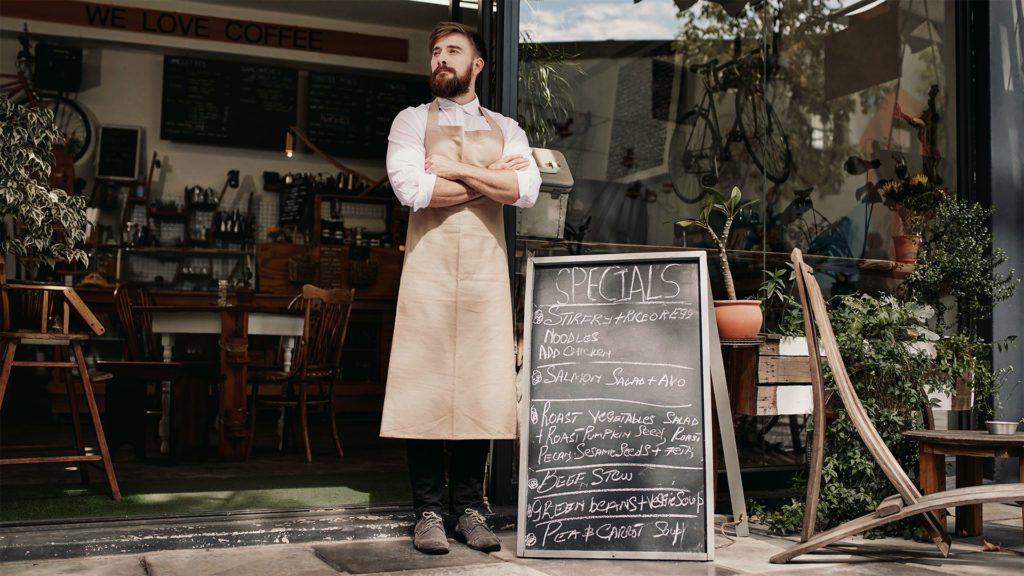 cameriere davanti alla porta del proprio bar