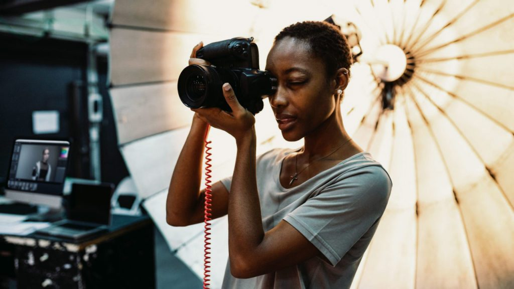 Giovane fotografo in piedi davanti a un ombrello riflettente