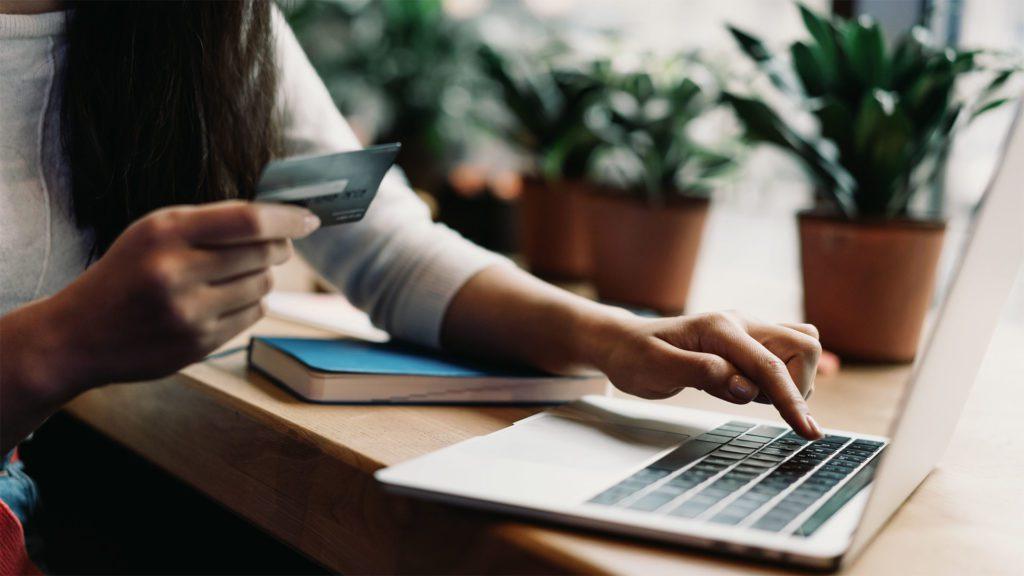 ragazza che fa acquisti online con in mano una carta di credito