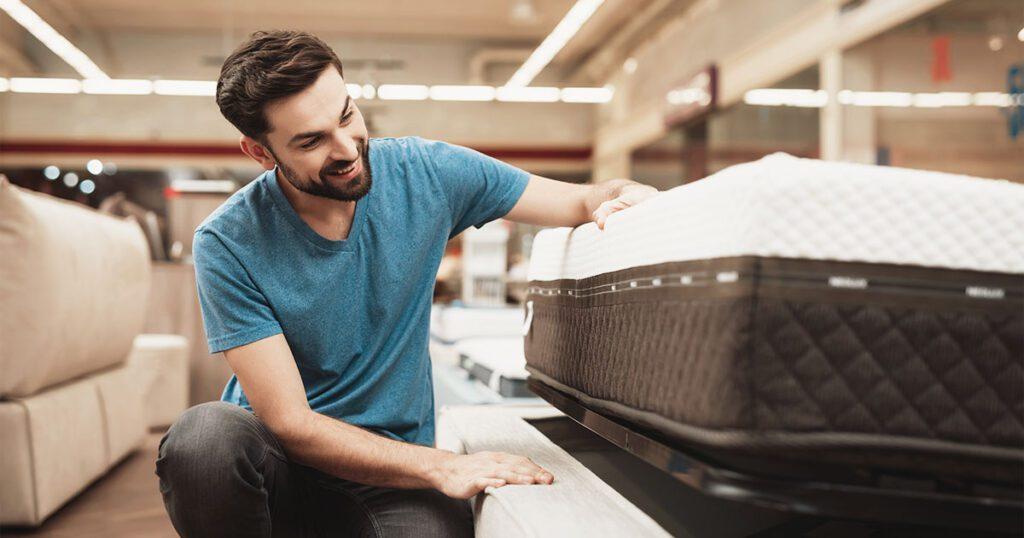 cliente che osserva un materasso all'interno di un negozio di arredamento
