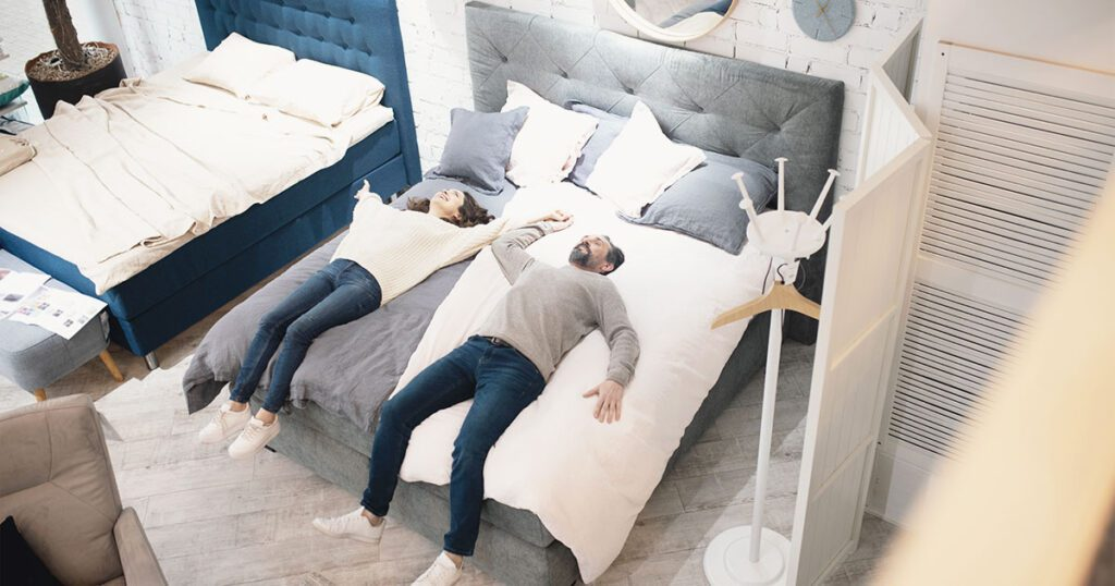 clienti che provano un letto di un negozio di arredamento