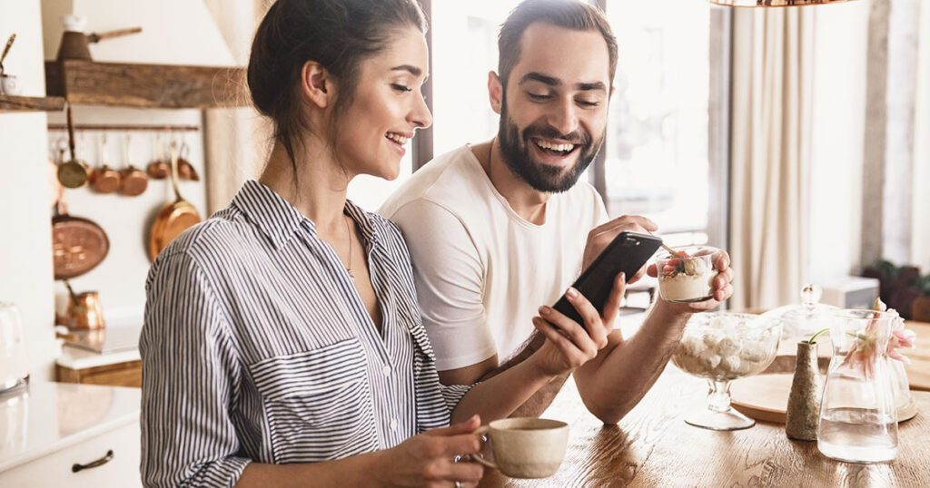 giovane coppia che legge un messaggio su WhatsApp durante la colazione