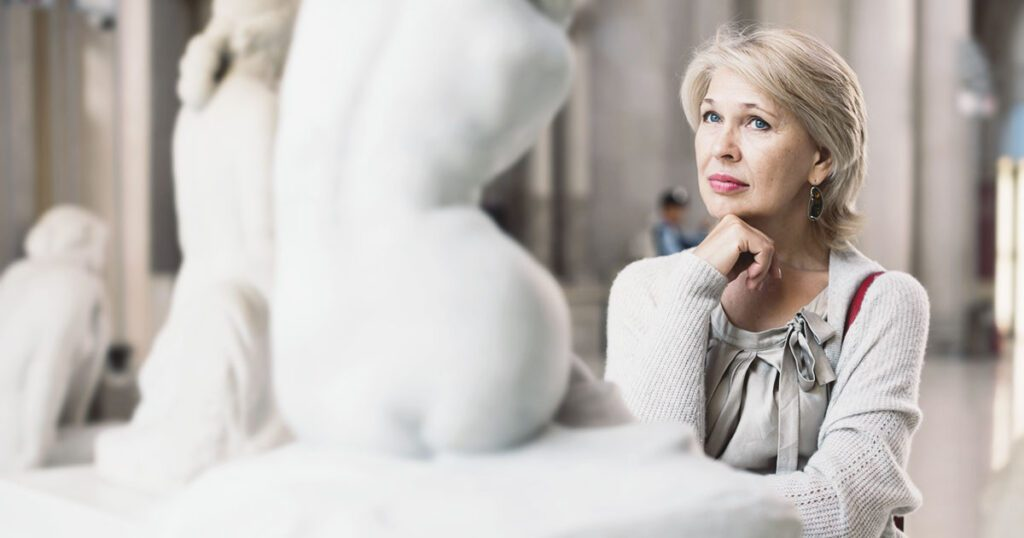 critico d'arte davanti ad una scultura in un museo